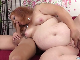 Redheaded plumper Scarlett Raven enjoys sucking laid hold of pang dicks