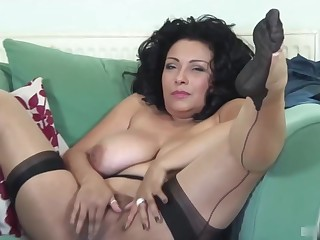 Hot mature brunette in erotic, black stockings is gently rubbing say no to shaved pussy and moaning